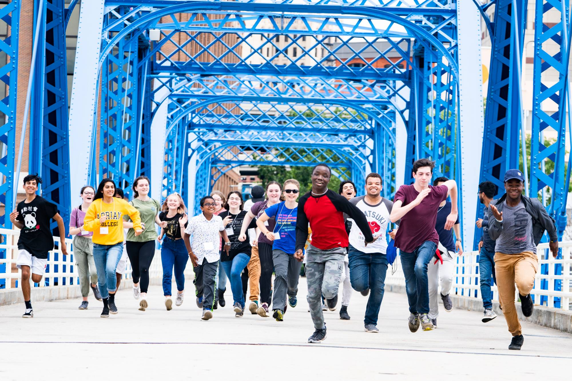 Students running enthusiastically across the Blue Bridge
